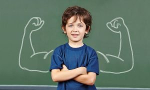 bambino a braccia incrociate davanti una lavagna con diregnate braccia che mostrano i muscoli