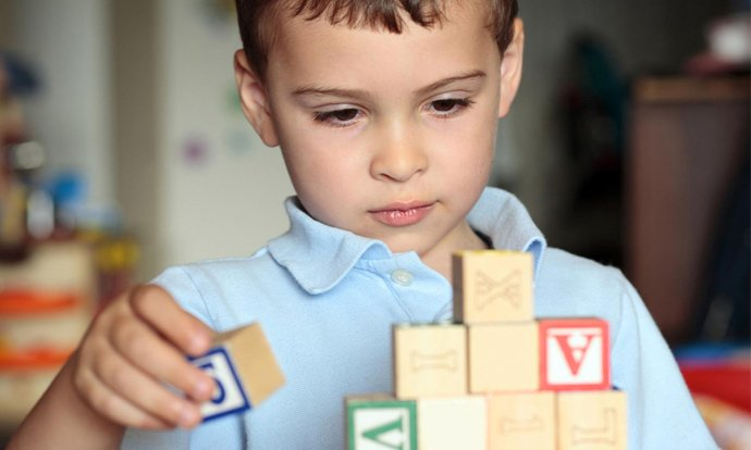 Un bambino gioca con i cubi di legno costruendo una piramide