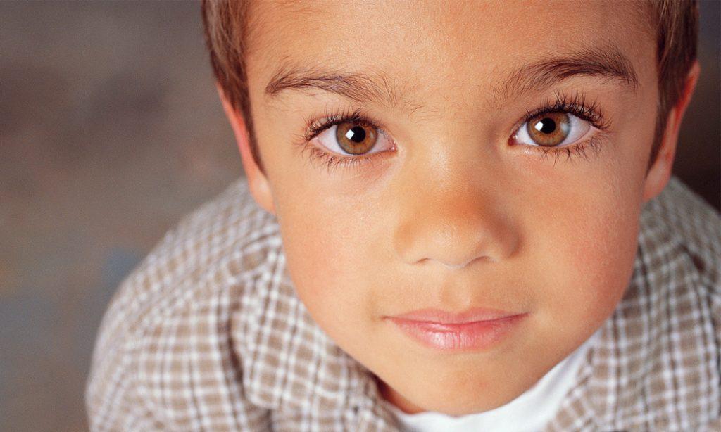 Primo piano di un bambino con gli occhi nocciola che  guarda