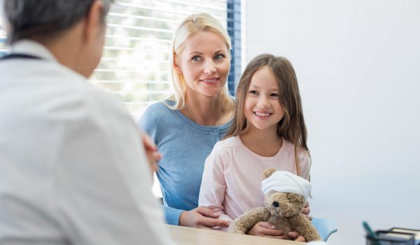 Mother and smiling daughter in a doctor office. Smiling young girl holding teddy bear toy with mother at pediatrician in hospital. Young mother and child meeting pediatrician in medical clinic.